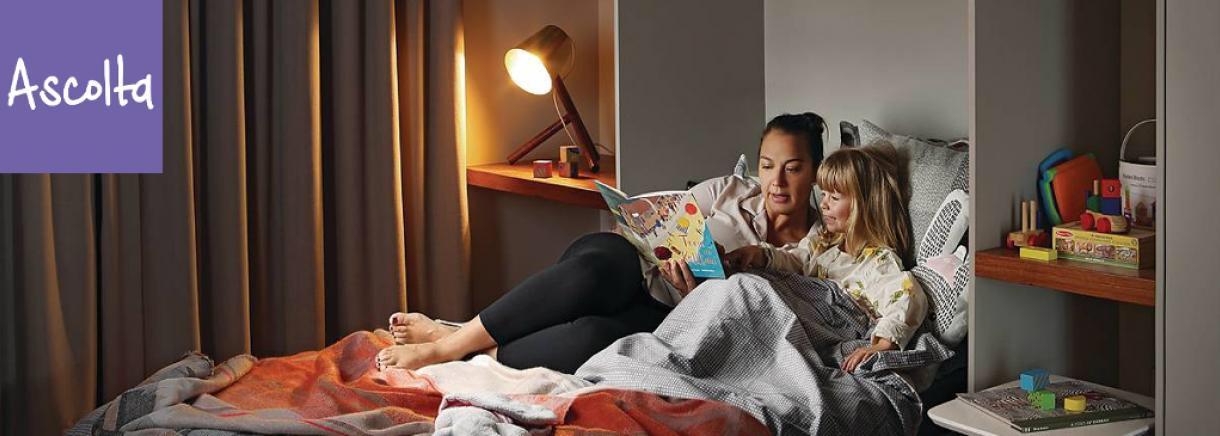Una madre e la figlia su un letto all'interno di un edificio multi comfort Saint-Gobain